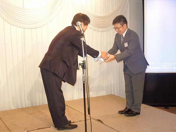 高野会長から梶尾会長へRPG設立15周年のお祝い贈呈